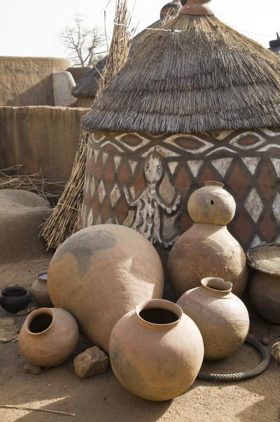 Africa, West Africa, Ghana, Sirigu. Handcrafted pottery leaning against traditional mud dwelling in Sirigu painted village