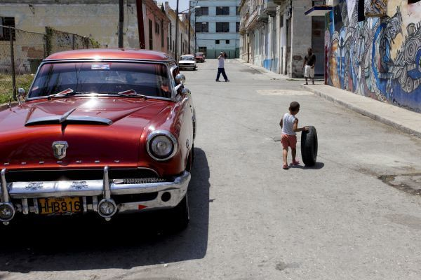 African Hamel district, Havana, Cuba, UNESCO World Heritage City. Child playing with old tire