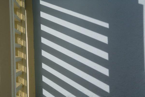 Caribbean, Netherlands Antilles, Curacao, Willemstad, Shadow of window shutters on blue wall