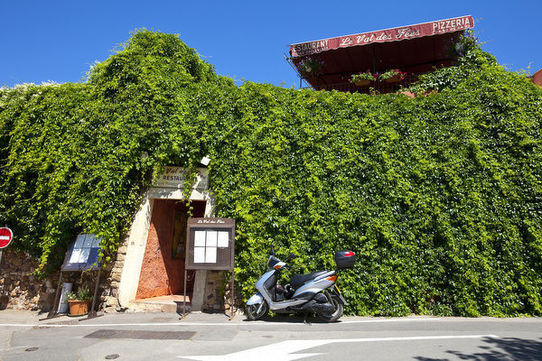 France, Provence, Roussillon. Motorcycle outside restaurant entrance. Credit as