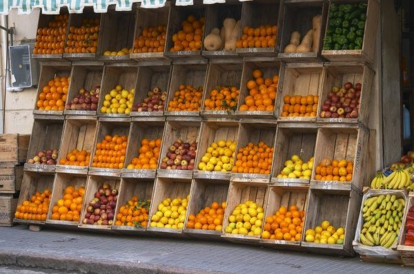 A Fruit And Vegetable Shop Displaying Products In Wooden Crates On The Street Tomatoes