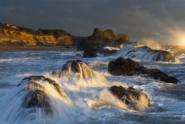 Waves crashing on rocks and washing down the sides at sunset