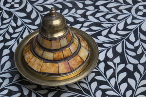 Africa, Morocco, Fes. A covered brass bowl with inlay of camel bone sites on a stone