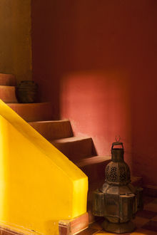 Africa, Morocco. An old lantern and jug on steps of a restored Kasbah with a texture