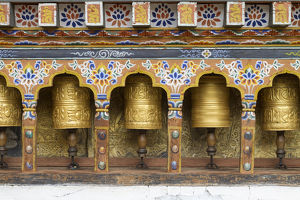 Bhutan. Spinning prayer wheels along a temple wall