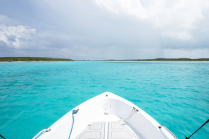 caribbean/exuma/boat drives clear aquamarine waters near staniel cay