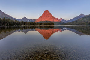 Calm reflection in Two Medicine Lake in Glacier National Park, Montana, USA