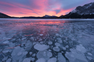 Canada, Alberta, Abraham Lake. Winter sunrise over lake and Mount Michener. Credit as