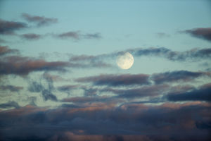 Canada, Nunavut Territory, Arviat, Full moon rises through clouds along west coast
