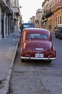 A classic old red Peugeot car parked on a street corner, probably from the 1950s
