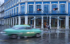Cuba, Havana. A classic car passes by in a rainstorm the city