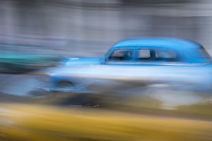 Cuba, Havana. Classic cars speed by in a blur along the streets of the city