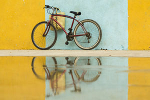 Cuba, Trinidad. Bicycle and reflection against yellow and blue walls