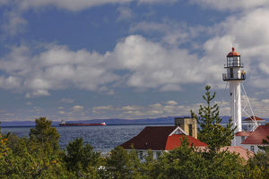 Freighter bound for Canada passing Whitefish Point Lighthouse, the oldest operating