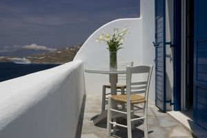 Greece, Mykonos, Hora. Balcony table and chairs with a docked cruise ship in the distance