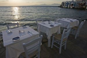 Greece, Mykonos, Hora. Three dinner tables overlooking the sea at sunset. Credit as