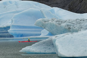 Kayaker exploring Grey Lake amid icebergs, Torres del Paine National Park, Chile