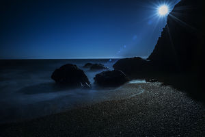 Long exposure of sun on beach and rocks on northern California coastline