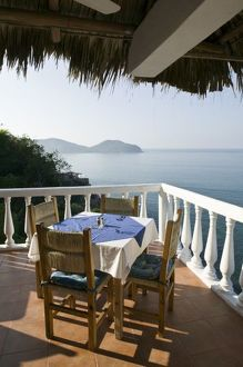 Mexico, Guerrero, Zihuatanejo. Cafe Table over Zihuatanejo Bay