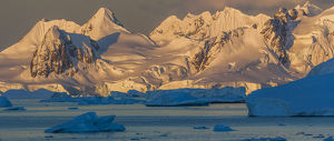 Morning light shines on the mountains of Antarctica, while the icebergs in the ocean