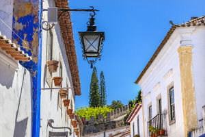 Narrow White Street 11th Century Castle Wall Medieval Town Lamp Obidos Portugal. Castle