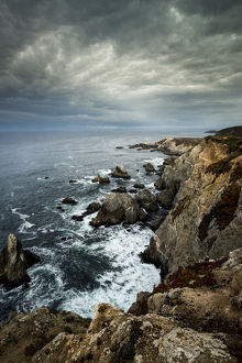 North America, USA, California. Clouds approaching the cliffs and surging waves at