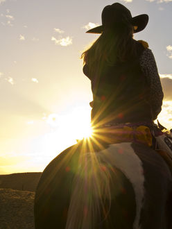 North America;USA;Wyoming;Shell;Big Horn Mountains;Cowgirl in silouette with sunset