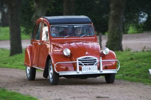 An old red Citroen 2CV car with a smiling woman driving, Elisa Trabal de Bouza owner