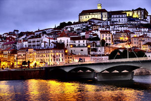 Portugal, Coimbra. Old Mondego River bridge and hillside view of Old University of Coimbra