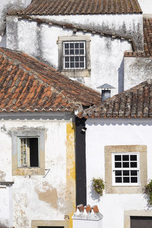 Portugal, Obidos. Ancient, red, terra cotta tiled roof tops, lines. Old windows