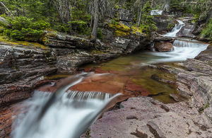 Red rocked Virginia Creek in Glacier National Park, Montana, USA