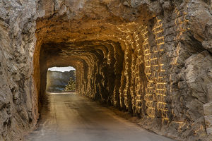 Tunnel on Iron Mountain Road lit by setting sun with view of Mount Rushmore near Keystone