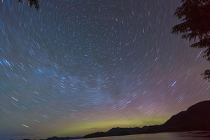US, AK, Ketchikan. Northern Lights glow on horizon with star trails rotating around
