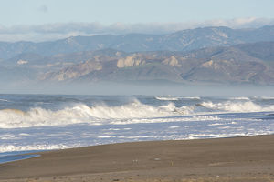 US, CA, Oxnard. Offshore wind blows spray back from waves. Ventura and foothills