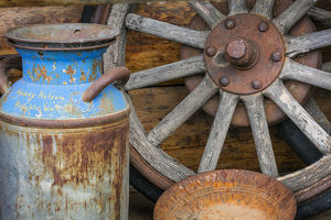USA, Alaska. Antique milk can, wagon wheel and gold pan