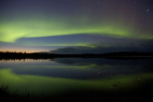 USA, Alaska, Bettles. Aurora borealis reflects in Vor Lake Waterlane