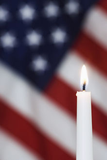 USA, California. Burning candle and American flag