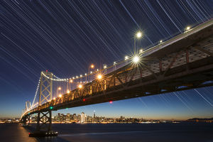 USA, California, San Francisco. Composite of star trails above Bay Bridge. Credit as