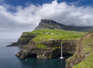 The waterfall near Gasadalur, one of the landmarks of Faroe Islands. The island Vagar