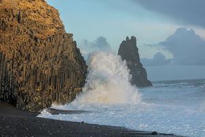 Waves from the North Atlantic Ocean crash into basalt columns at the Black Beach near Vik