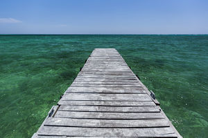 A wood dock in the foreground with clear green water and blue skies near the Isle of Youth