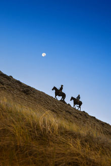Two wranglers riding horses up a hill with full moon in backround at blue hour